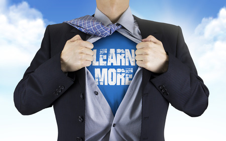 comprehend: businessman showing Learn more words underneath his shirt over blue sky Stock Photo