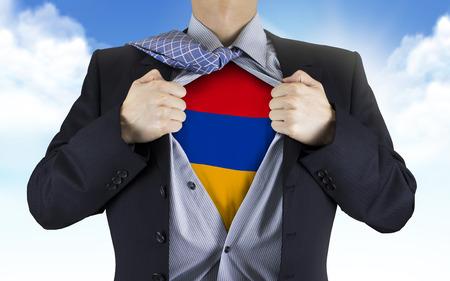 armenia: businessman showing Armenia flag underneath his shirt over blue sky