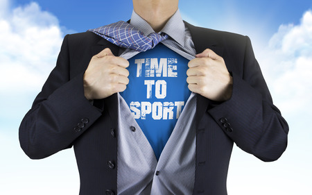 fitness goal: businessman showing Time to sport words underneath his shirt over blue sky Stock Photo