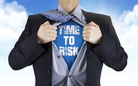 underneath: businessman showing Time to risk words underneath his shirt over blue sky