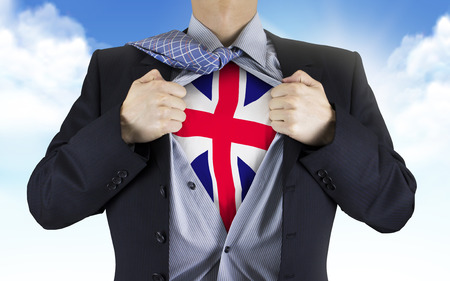great britain flag: businessman showing Great Britain flag underneath his shirt over blue sky