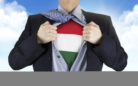underneath: businessman showing Hungarian flag underneath his shirt over blue sky