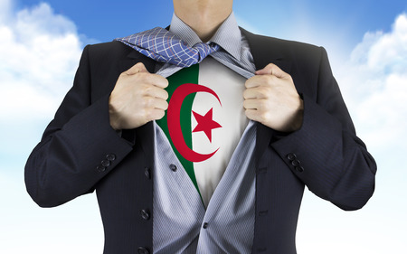 businessman showing Algeria flag underneath his shirt over blue sky photo