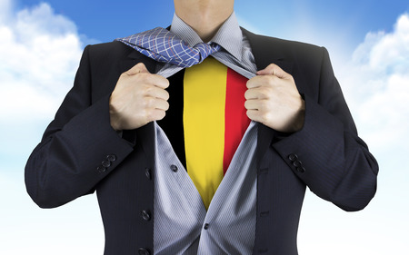 underneath: businessman showing Belgium flag underneath his shirt over blue sky