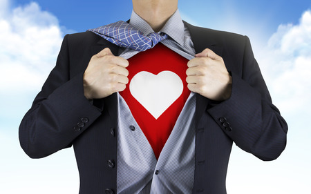 underneath: businessman showing heart icon underneath his shirt over blue sky Stock Photo