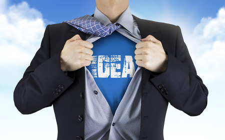 underneath: businessman showing Idea word underneath his shirt over blue sky Stock Photo