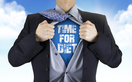 underneath: businessman showing Time for diet words underneath his shirt over blue sky Stock Photo
