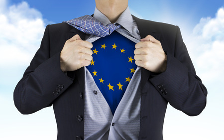 underneath: businessman showing Europe flag underneath his shirt over blue sky