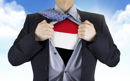 underneath: businessman showing Yemen flag underneath his shirt over blue sky Stock Photo