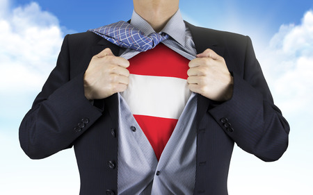 underneath: businessman showing Austria flag underneath his shirt over blue sky Stock Photo