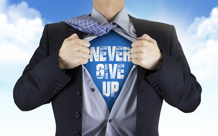 never: businessman showing Never give up words underneath his shirt over blue sky