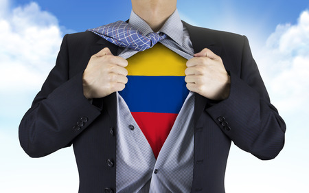 underneath: businessman showing Colombia flag underneath his shirt over blue sky