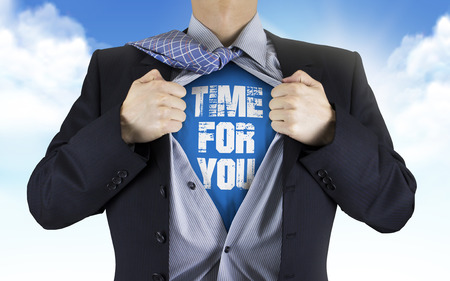 underneath: businessman showing Time for you words underneath his shirt over blue sky