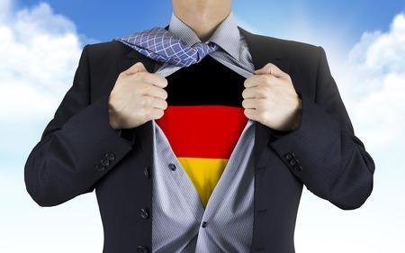 푸른 하늘 위에 그의 셔츠 밑에 독일 국기를 보여주는 사업가