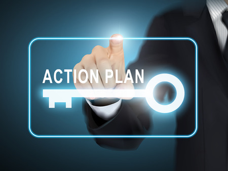 action plan: male hand pressing action plan key button over blue abstract background