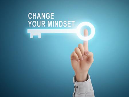 mannelijke hand drukken verandering uw mentaliteit sleutel knop op blauwe achtergrond