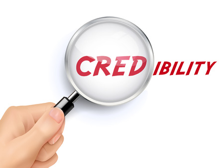 credibility: credibility word showing through magnifying glass held by hand