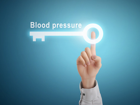 blood pressure monitor: male hand pressing blood pressure key button over blue abstract background