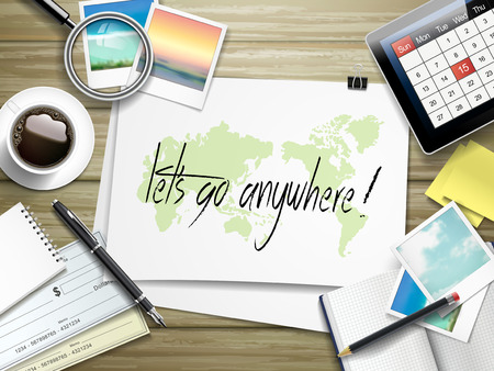 prepare: top view of travel items on wooden table with let us go anywhere written on paper