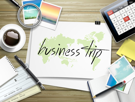 top view of travel items on wooden table with business trip written on paper