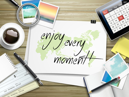 mindful: top view of travel items on wooden table with enjoy every moment written on paper