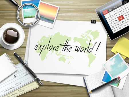 top view of travel items on wooden table with explore the world written on paper