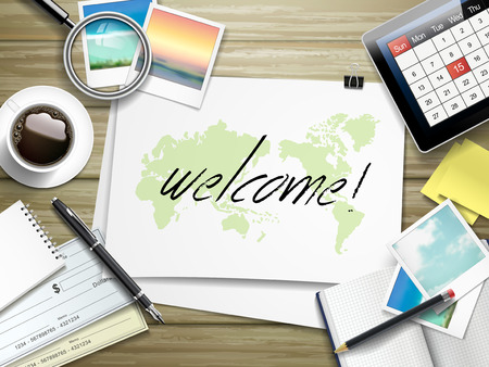 eager: top view of travel items on wooden table with welcome word written on paper