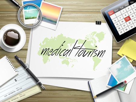 medical preparation: top view of travel items on wooden table with medical tourism written on paper