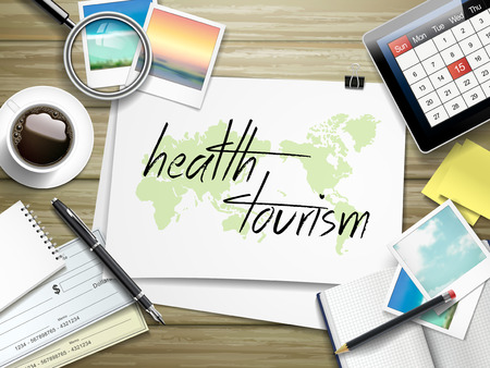 medical preparation: top view of travel items on wooden table with health tourism written on paper