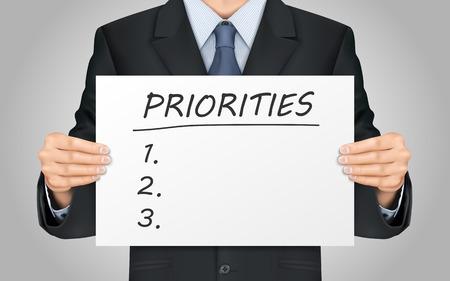 prioridades: close-up mira empresario sosteniendo prioridades cartel palabra