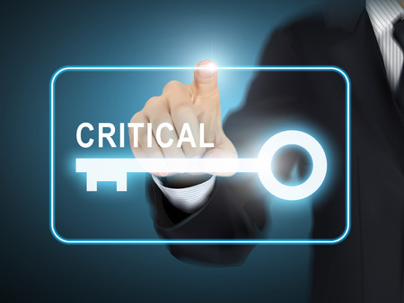 crucial: male hand pressing critical key button over blue abstract background