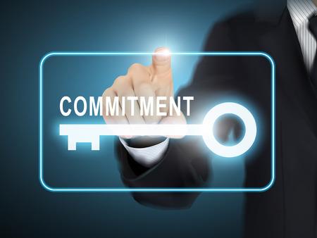 compromiso: mano presionando el botón clave compromiso masculino sobre fondo abstracto azul