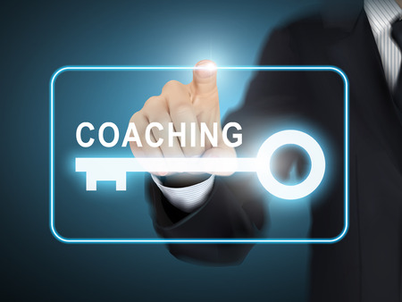 career coach: male hand pressing coaching key button over blue abstract background
