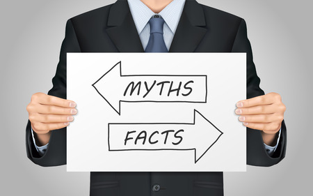 factual: close-up look at businessman holding myths or facts poster