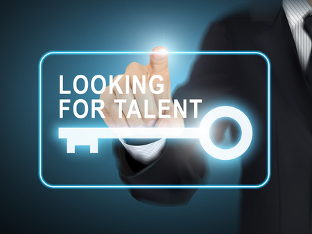 press agent: male hand pressing looking for talent key button over blue abstract background