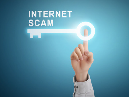 scam: male hand pressing internet scam key button over blue abstract background