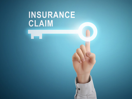 insurance claim: male hand pressing insurance claim key button over blue abstract background