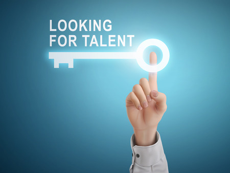 staffing: male hand pressing looking for talent key button over blue abstract background