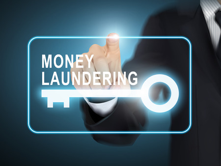 money laundering: male hand pressing money laundering key button over blue abstract background