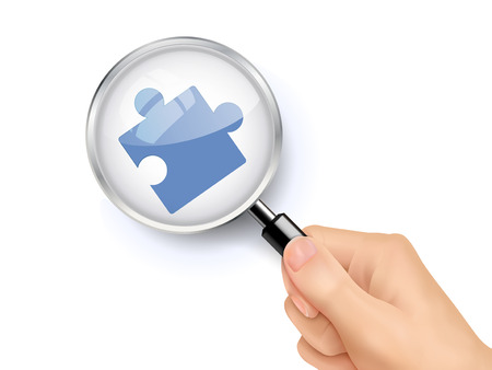 puzzling: jigsaw symbol showing through magnifying glass held by hand