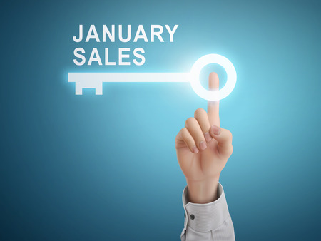 auction off: male hand pressing January sales key button over blue abstract background