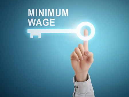 male hand pressing minimum wage key button over blue abstract background