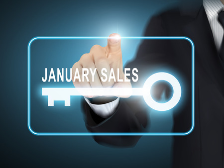 auctioneer: male hand pressing January sales key button over blue abstract background