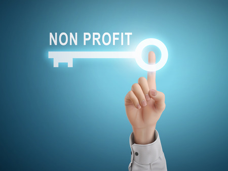 non profit: male hand pressing non profit key button over blue abstract background