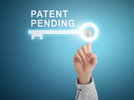 patente: mano masculina presionando patente pendiente bot�n de la llave sobre fondo azul abstracto
