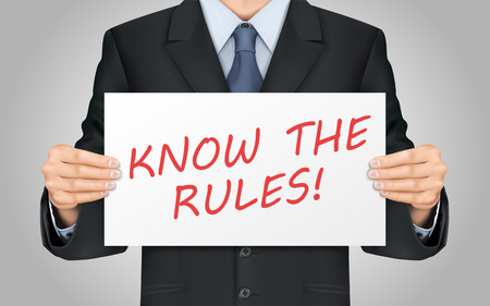 regulation: close-up look at businessman holding know the rules poster