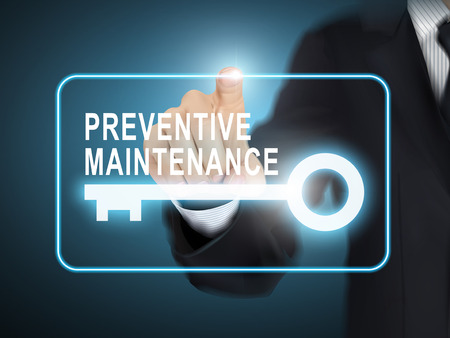 preventive: male hand pressing preventive maintenance key button over blue abstract background