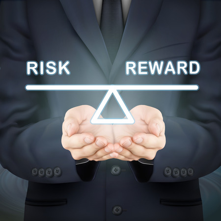 balance scale: close-up look at businessman holding risk and reward seesaw