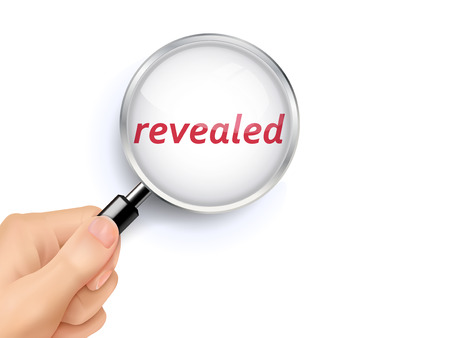 revealed: revealed word showing through magnifying glass held by hand