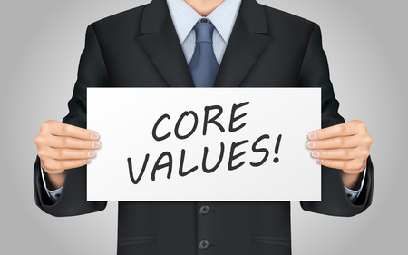 virtue: close-up look at businessman holding core values poster